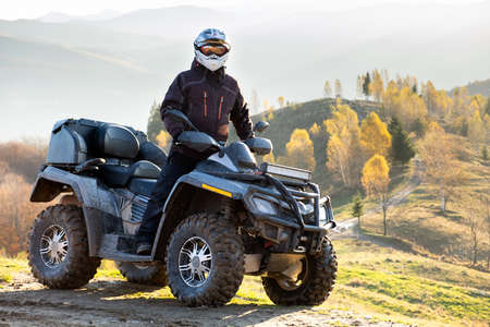 Happy male driver in protective helmet enjoying extreme ride on atv quad motorbike in autumn mountains at sunset. Reklamní fotografie