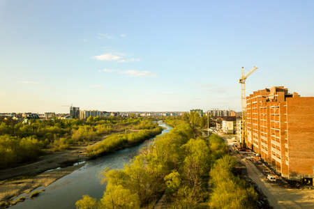 Aerial view of tall residential apartment buildings under construction and Bystrytsia river in Ivano-Frankivsk city, Ukraine. Imagens