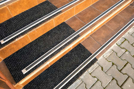 Closeup of ceramic tiles covering porch stairs with rubber anti slippery stripes on it. Imagens