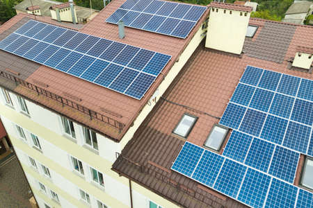 Aerial view of solar power plant with blue photovoltaic panels mounted of apartment building roof. Imagens