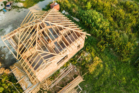 Aerial view of unfinished brick house with wooden roof structure under construction. Imagens - 164304581