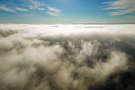 Aerial view from above of white puffy clouds in bright sunny day. Imagens