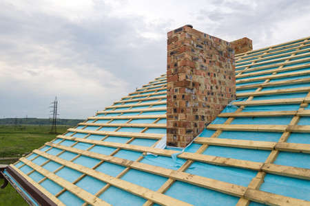 Aerial view of a wooden roof frame of brick house under construction. Imagens