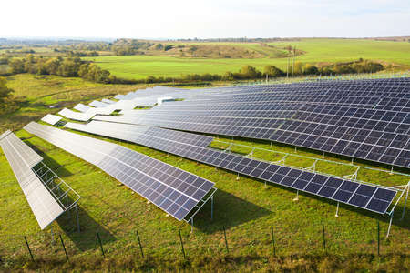 Aerial view of solar power plant under construction on green field. Assembling of electric panels for producing clean ecologic energy. Imagens