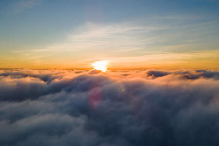 Aerial view of bright yellow sunset over white dense clouds with blue sky overhead.