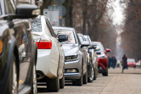 Cars parked in a row on a city street side. Imagens