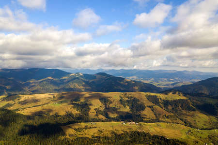 Aerial view of bright green spruce and yellow autumn trees in fall forest and distant high mountains. Imagens