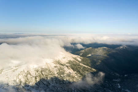 Aerial view from above of white puffy clouds covering snowy mountain tops in bright sunny day. Imagens - 164304638
