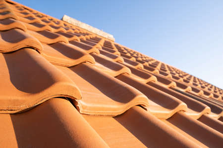 Overlapping rows of yellow ceramic roofing tiles covering residential building roof. 免版税图像