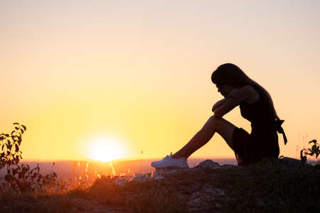 Young depressed woman in black short summer dress sitting on a rock thinking outdoors at sunset. Fashionable female contemplating in warm evening in nature.