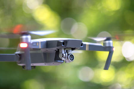 Drone copter with blurred propellers and video camera flying in air.