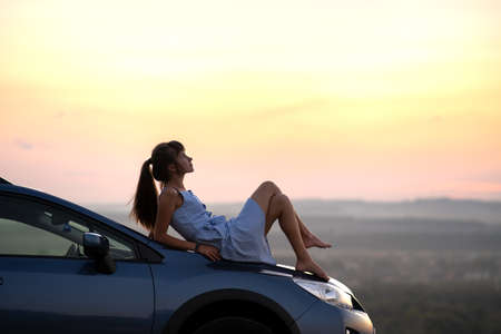 Happy young woman driver in blue dress laying on her car hood enjoying warm summer day. Traveling and vacation concept.