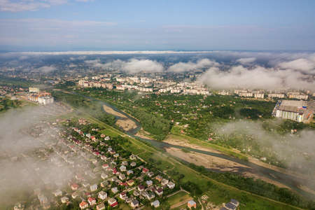 Aerial view of white clouds above a town or village with rows of buildings and curvy streets between green fields in summer. Countryside landscape from above. Reklamní fotografie