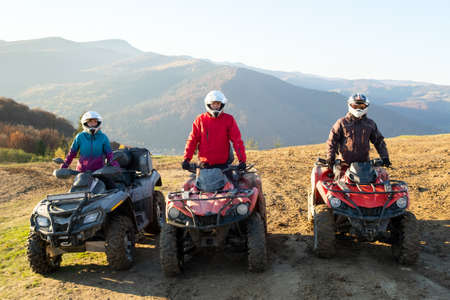 Happy drivers in protective helmets enjoying extreme riding on ATV quad motorbikes in summer mountains at sunset.