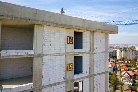 Aerial view of high residential apartment building with storey numbers on wall under construction. Real estate development. Reklamní fotografie