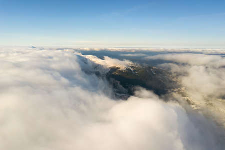 Aerial view from above of white puffy clouds covering snowy mountain tops in bright sunny day. Reklamní fotografie