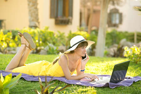 Woman on vacation lying on green grass lawn working on laptop connected to wireless internet having conversation on mobile cell phone in summer park. Doing business and studying remotely concept.