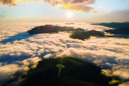 Aerial view of vibrant sunrise over mountain hills covered with evergreen spruce forest in autumn. Reklamní fotografie