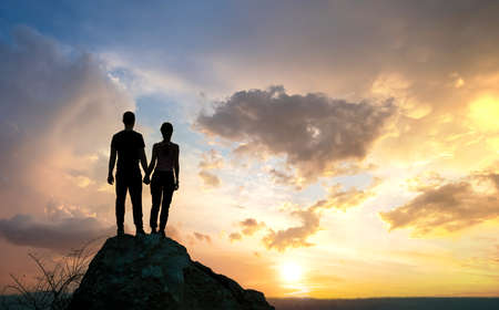 Man and woman hikers standing on a big stone at sunset in mountains. Couple together on a high rock in evening nature. Tourism, traveling and healthy lifestyle concept.