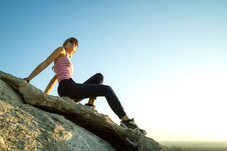 Woman hiker sitting on a steep big rock enjoying warm summer day. Young female climber resting during sports activity in nature. Active recreation in nature concept. Reklamní fotografie