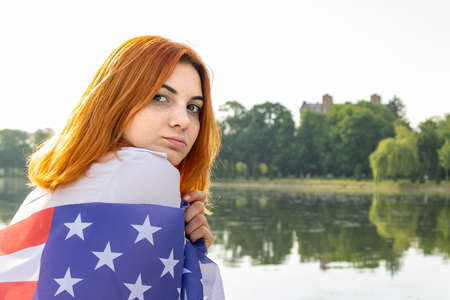 Portrait of sad red haired girl with USA national flag on her shoulders. Young woman celebrating United States independence day. Reklamní fotografie