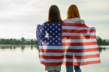Two young friends women with USA national flag on their shoulders hugging together outdoors on lake shore. Patriotic girls celebrating United States independence day. International day of democracy concept.
