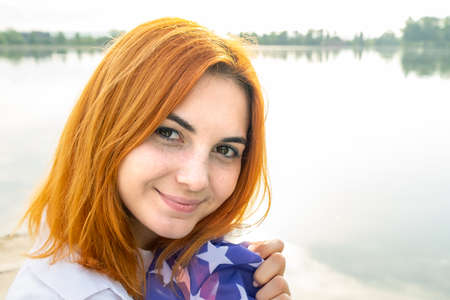 Portrait of happy smiling red haired girl. Positive young woman looking in camera outdoors. Reklamní fotografie