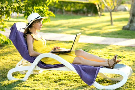 Young woman resting on chair on green grass lawn working on computer laptop connected to wireless internet in summer park. Doing business and studying remotely during quarantine on vacations concept.