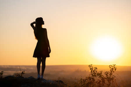 Dark silhouette of a young woman in summer dress standing outdoors enjoying view of nature at sunset. Reklamní fotografie
