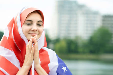 Portrait of young refugee woman with USA national flag on her head and shoulders. Positive muslim girl praying outdoors.