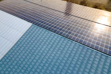 Aerial view of surface of blue photovoltaic solar panels mounted on building roof for producing clean ecological electricity. Production of renewable energy concept. Reklamní fotografie