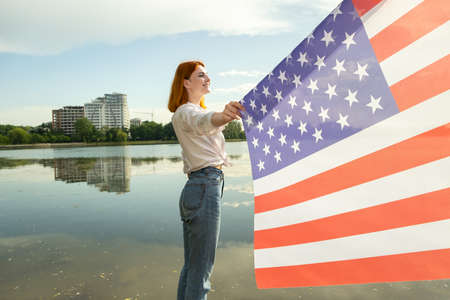 Happy red haired woman with United States national flag in her hand. Positive girl celebrating US independence day. International day of democracy concept. Reklamní fotografie