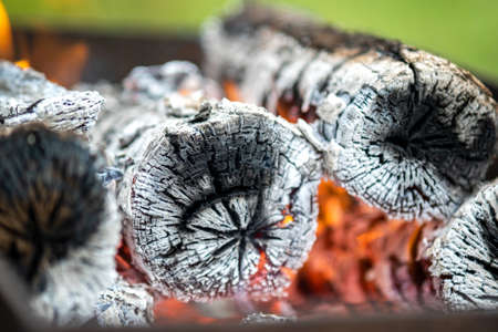 Close up of brightly burning wooden logs with yellow hot flames of fire.