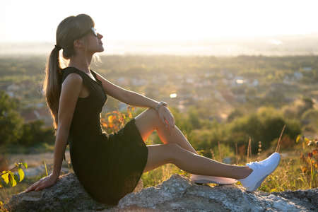 Young elegant woman in black short dress and white sneaker shoes sitting on a rock relaxing outdoors at summer evening. Fashionable lady enjoying warm sunset in nature. Reklamní fotografie