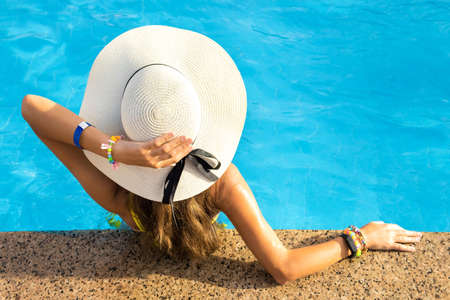 Back view of young woman with long hair wearing yellow straw hat relaxing in warm summer swimming pool with blue water on a sunny day.