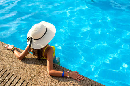 Top down view of young woman wearing yellow straw hat resting in swimming pool with clear blue water on summer sunny day.