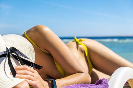 Close up of young woman hip and shoulder laying on beach chair at sea shore sunbathing. Reklamní fotografie
