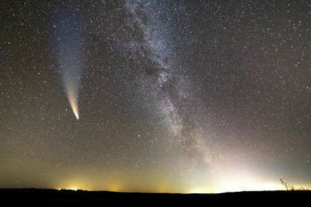 Night landscape of dark hill with stars covered sky and Neowise comet with light tail. Reklamní fotografie