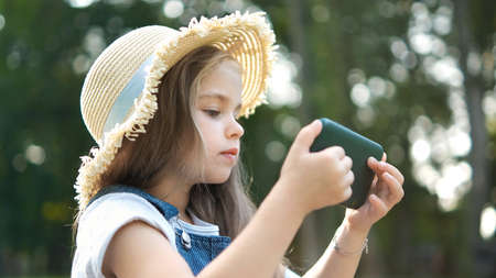 Happy smiling child girl watching in her mobile phone outdoors in summer.