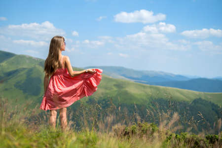 Young woman in red dress standing on grassy field on a windy day in summer mountains enjoying view of nature.