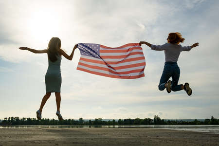 Two young friends women holding USA national flag jumping up together outdoors at sunset. Silhouette of girls celebrating United States independence day.