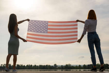 Silhouette of two young friends women holding USA national flag up in their hands standing together. Patriotic girls celebrating United States independence day.