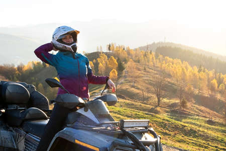 Happy female driver in protective helmet enjoying offroad riding on ATV quad motorbike in autumn mountains at sunset.