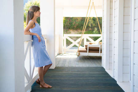 Side view of young woman in blue dress looking on nature on balcony. Concept of enjoying fresh air and good weather. Standard-Bild