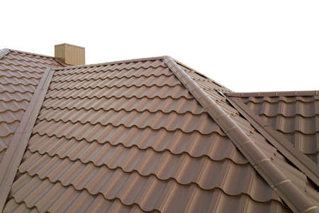 House roof structure covered with brown metal tile sheets.