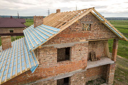 Aerial view of a brick house with wooden roof frame under construction.