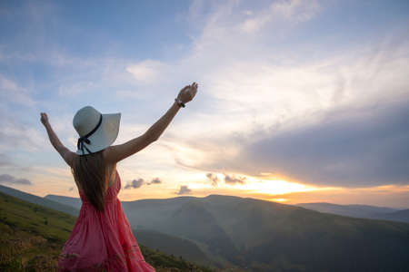 Young woman in red dress standing on grassy field on a windy evening in autumn mountains raising up her hands enjoying view of nature.