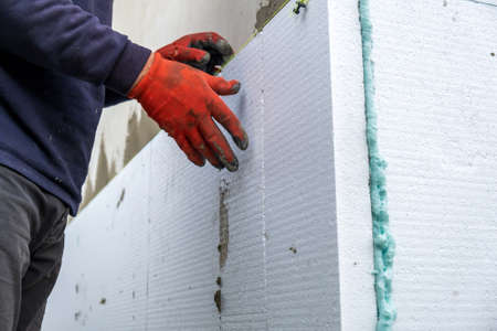 Construction worker installing styrofoam insulation sheets on house facade wall for thermal protection. Zdjęcie Seryjne