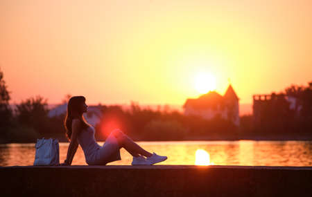 Lonely young woman sitting alone on lake shore enjoying warm evening. Wellbeing and relaxing in nature concept. Banque d'images