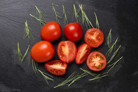 Ripe red tomatoes and salad leaves on black dark stone background. Banco de Imagens